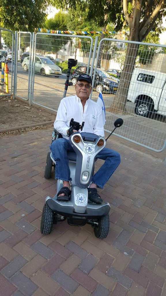 Old gentleman sitting on a blue Titan 4, one of the disability scooters